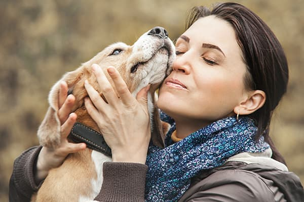 woman nuzzling a dog's face